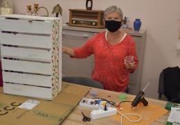 Kobieta maluje skrzynkę drewnianą